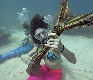 "Participants might even catch ""mermaids"" and other costumed characters attempting to perform their own marine melodies — pretending to play underwater musical instruments."